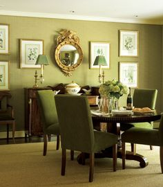 Monochromatic moss green dining room with textured wallpaper, dark wood furniture and pops of gold.
