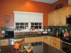 burnt orange kitchen, black granite countertops, glass tile backsplash