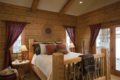 A rustic bedroom in a modern timber frame home. Photo Courtesy of PrecisionCraft Log  Timber Homes