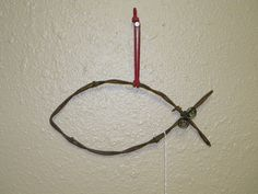 """This fish shaped decoration is made from clockwise twist, flat barbed wire from Texas. It has a stable rusty patina. The shape is held together with tie wire and has a hanger of your choice of natural jute, green jute, red leather, or black leather. Because the item is handmade, the size will vary, but will typically be about 7""""-8"""" wide and 3""""-4"""" high. This item is good for hanging on a wall or as a Christmas tree ornament."""