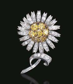 A DIAMOND AND COLORED DIAMOND BROOCH, BY TRABERT & HOEFFER, MAUBOUSSIN  Designed as a daisy, the circular-cut yellow diamond cluster pistil, extending sculpted old European, circular and single-cut diamond petals, from a single, circular and baguette-cut diamond stem and leaf, mounted in platinum, in a Mauboussin black leather fitted box Signed Trabert & Hoeffer, Mauboussin, no. 4235