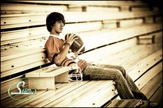 Hangin out in the stands with jersey, helmet and football in this senior portrait