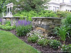 These elegant plantings and stone pillars help this historic home fit into the landscape. Landscaping by Switzers Nursery and Landscape in Northfield, MN.