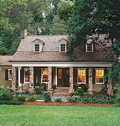 Great style home. Stone columns, dormer windows, long porch, and simple landscaping.