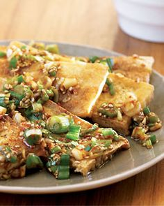 Seasoned Tofu   Ingredients  One 18-ounce package firm tofu  2 green onions, chopped  2 cloves garlic, minced  2 tablespoons soy sauce  1 tablespoon Asian sesame oil  1 tablespoon toasted sesame seeds  1 teaspoon Korean chile powder