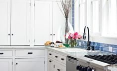 Crisp white cabinetry in this coastal kitchen keeps clutter to a minimum. To bring a pop of color into the room, the seaside palette is reflected with counters made of recycled glass and cement and a vibrant glass subway tile backsplash.