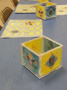 Table centerpieces made from old CD cases with melted crayon shavings melted with an iron between two sheets of wax paper for the background and clip art from online. Also created woven place mats for the tables at our Blue and Gold banquet.