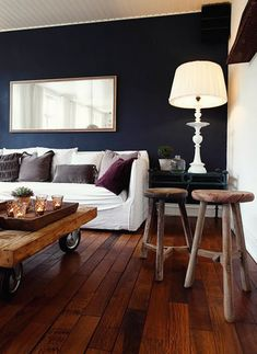 Great color sceme and home vibe going here: Especially love the wood floors and furniture mixed with the navy walls and purple, gray and white mix throughout the room.