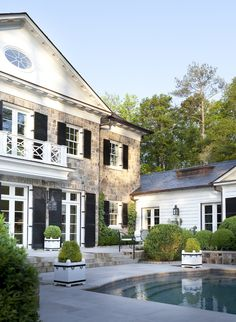 stone house with white trim, black shutters, mouldings, potted boxwood.