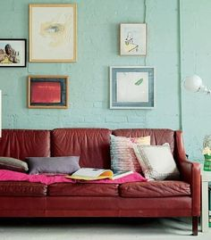 Randomly place paintings on a brick wall behind an old couch.  Love the minty green paired with maroon.