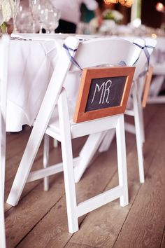 Mr. and Mrs. chalk board signs on the back of the bride and groom's chairs - photo by Emily Delamater Photography | via junebugweddings.com