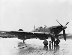 """F/L J R Sterne RCAF of No. 174 Squadron RAF standing beside his Hurricane Mark IIB, HV894 """"Our John"""" (named after Wing Commander John Gillan, and paid for by a fund set up by his mother after he was reported missing in 1941), at Odiham, Hampshire. (IWM)"""