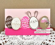 A variety of die cut eggs are featured front and center on this handmade Easter card.  Several have been popped up on dimensional foam, including the Easter basket full of flowers and the bunny with the floppy years.