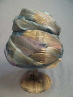 Vintage Christian Dior hat, made up of turquoise tulle and golden feathers.