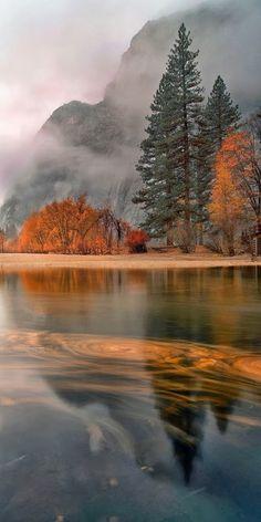 """Leaves swirl at sunset in a light November rain on the Merced River in Yosemite Village, California."""