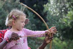 Young girl learns to do traditional bow and arrow with professional Asilia Africa guide at the Mara Bush houses / Kenya /Maasai Mara. www.asiliafrica.com