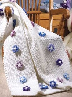 Posies for Baby - This baby afghan features a white center and a sprinkling of blue and purple flowers around the border. The petals of each flower are formed by variation of the Roll Stitch. Crocheted with worsted weight yarn and G and H size hooks, this afghan makes a perfect gift for that new baby. Skill Level: Easy  Designed by Bonnie Pierce free PDF from freepatterns.com
