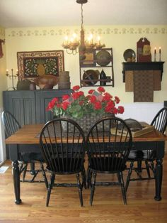 A lovely dining room filled with period 18-19th century American antiques. The red flowers on the table adds the perfect color to an otherwise warm room.