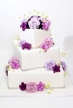White fondant wedding cake with square tiers decorated with pink and purple roses and orchids. Cake by Carlo's Bakery.