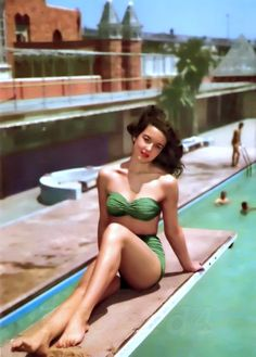 Vintage Bikini from the 60s, mid-century. Girl beside a swimming pool wearing a green bikini.