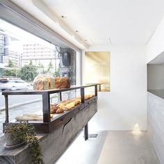 This bakery shop in Osaka was refurbished by Japanese firm Ninkipen! with bread displayed on a wooden sleeper and the kitchen sat behind an exposed concrete counter.
