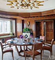The dining room's brass-and-frosted-glass light fixture is a 1964 design by Gio Ponti, the oak-and-bronze table is by Hervé Van der Straeten from Ralph Pucci International, and the vintage chairs are by Carlo di Carli and are covered in a Christopher Hyland cotton. Couturier
