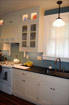 Dark counters to go with white & blue kitchen.