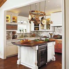 A copper 1950s Chambers stove, beadboard cabinet doors, and Calacata Gold marble give this cottage kitchen updated vintage charm.   Photo: Dominique Vorillon   thisoldhouse.com