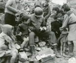 Italian children gather around a GI with hopes of sharing the contents of a gift package he received from home.