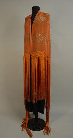 ART DECO CHIFFON and GOLD LAME FRINGED SHAWL. Burnt orange rectangle with a lame pattern of stylized roses in a grid with bands of wavy lines and columns of squares, the ends having long knotted fringe. whitakerauction.com