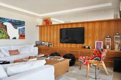 Sala de tv com painel de madeira.