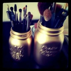 Mason jars spray-painted gold as makeup brush holders