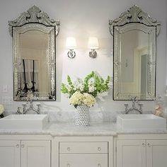 bathrooms - ivory bathroom vanity, built-in vanity, ivory vanity, dual vanity, his and hers sinks, white dual vanity, dual sinks, crystal hardware, marble counters, marble countertops, vase, flowers, counter mount faucet, counter mounted faucet, traditional style faucet, vessel sink, modern vessel sink, square vessel sink, white walls, white wall color, venetian mirror, venetian vanity mirror, polished nickel sconce, ivory double vanity,
