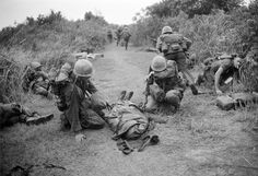 A U.S. Marine wipes tears from his face as he kneels beside a body wrapped in a poncho during a firefight near the demilitarized zone between North and South Vietnam, Sept. 18, 1966. Other casualties lie at the side of the road as fighting continued.