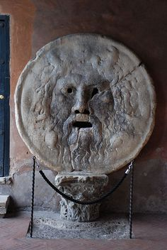 """The famous """"Mouth of Truth"""" (Bocca della Verita) located in the portico of the church of Santa Maria in Cosmedin in the Forum Boarium. The sculpture is thought to be an ancient manhole cover of a water god.    Legend has it that the Mouth of Truth is a lie detector, if you told a lie with your hand in the mouth of the sculpture, it would be bitten off."""