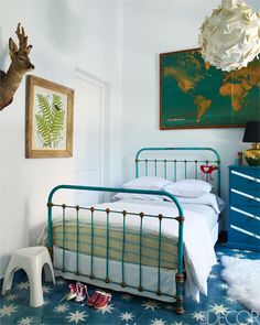 A vintage iron bed comes and a vintage map in this child's bedroom.