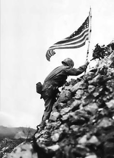 US Marine Lt. Col. RP Ross, JR braving sniper fire to climb to the stop of Shuri castle on Okinawa to place the US flag, 29 May 1945