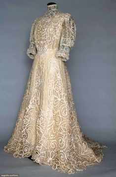 "TRAINED CREAM LACE TEA GOWN, c. 1906  New York City  1 piece, handmade Battenburg lace & machine made Valenciennes lace inserts, high collar, ruffled lace elbow length sleeves, B 38"", W 25"", (.5"" x 2"" hole in brides between Battenburg lace at skirt back, shattered silk taffeta lining) very good. Montclair Historical Society"