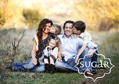 Family photo shoot. Kids kissing parents cheek
