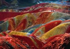 This is a unique geological phenomenon known as Danxia landform, which can be observed in several places in China.  The color is the  result of an accumulation for millions of years of red sandstone and other rocks.