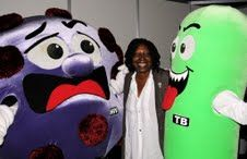 Whoopie Goldberg with HIV & Tuberculosis mascots in DC for World AIDS Conference 2012.