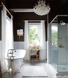 designer Annie Brahler chose the master bath's chocolaty walls to play up the brilliant whites of a recycled tub, curtains in Kally Almost White sheer from Hancock Fabrics, and Daltile floor and shower tiles. The crystal light fixture is a 1980s update of old-school glamour. - House Beautiful