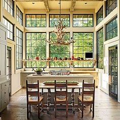 Space-Saving Farm Table | Combined with a classic farmhouse table and chairs, the clean-lined bench—attached to the island and painted the same color as the cabinets—saves valuable floorspace. | SouthernLiving.com