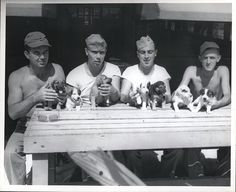 """""""Somewhere in the Marshall Islands, Cute aren't they?"""" (puppies of course!), ca. 1941-1945 by Marine Corps Archives & Special Collections, via Flickr. These four Marines have taken over the job of being foster mother to the pups, after their real mother left behind by the Japanese, gave birth to a litter of 13 and couldn't take care of all of them. From the Photo Collection (COLL/3948), Marine Corps Archives & Special Collections"""