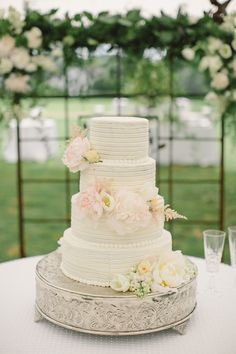 textured white cake with pale pink blooms