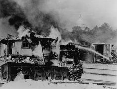 """""""Shacks, put up by the Bonus Army on the Anacostia flats, Washington, D.C., burning after the battle with the military. The Capitol in the b..."""