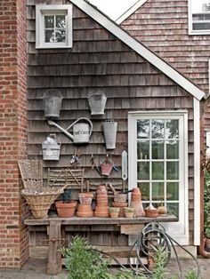 """Lovely garden styling!! Pinner wrote, """"Garden Workstation - This circa -1900 oak woodworker's table was drafted into service as a potting station, vintage pails and watering cans were then hung on the cottage's exterior wall."""""""