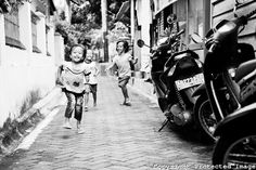 Black and White Photo of Excited Kids Running Along a Side Street in Yogyakarta, Java, Indonesia  ::: Matthew Williams-Ellis :::