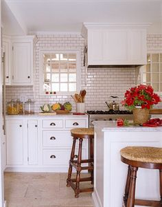 The gleaming white kitchen is the previous owners' renovation, with walls clad in subway tiles from Ann Sacks. To warm it up, Scheerer added wooden rush-seat stools.