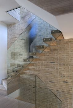 Open riser staircase supported by single brick wall and no visible stringers with attached glass sheet railing.  Butterfly Loft Apartment, London, 2011 by Tigg + Coll Architects #architecture #design #stair #glass